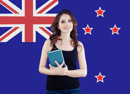 Happy student girl with book against the New Zealand flag background