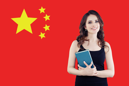 Study, internship and work in China concept. Beautiful smart woman smiling on chinese flag background