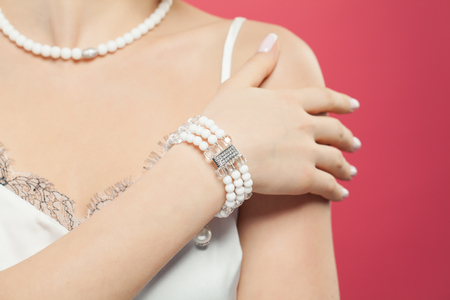 Woman hand wearing silver jewelry bracelet with pearls on pink background