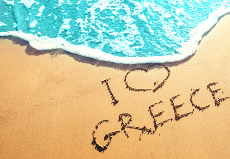 Golden sandy beach with the inscription on the sand by the sea - I love Greece. Best beaches in Europe