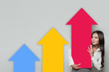 Geschäftsfrau, die steigende Pfeilspalten zeigt, die das Geschäftswachstum darstellen. Geschäftserfolg und Share-Up-Konzept Standard-Bild