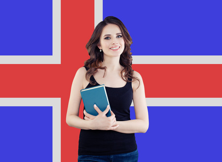 Learn Icelandic language concept. Portrait of happy pretty woman student against the Iceland flag background Reklamní fotografie