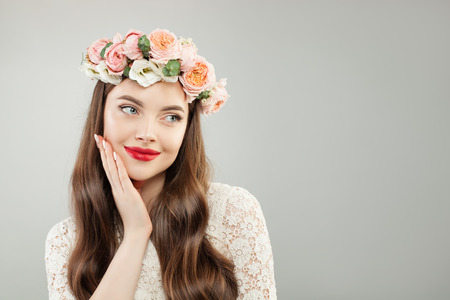 Young woman in summer flowers wreath. Pretty model with red lips makeup and cute smile portrait Stockfoto