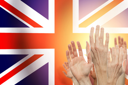 People raising hands and United Kingdom flag on background. Patriotic concept