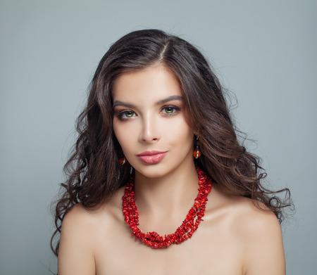 Femme modèle brune parfaite avec du maquillage, de longs cheveux bouclés et un collier de corail rouge Banque d'images