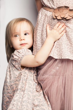 Baby girl holding her mother skirt. Childhood concept Stock Photo