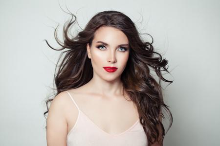 Donkerbruine modelvrouw met lang perfect haar en rode lippenmake-up op witte background Stockfoto