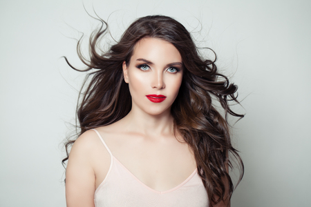 Femme modèle brune aux longs cheveux parfaits et maquillage des lèvres rouges sur fond blanc Banque d'images