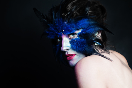 Halloween character. Model woman with blue bird makeup on black background