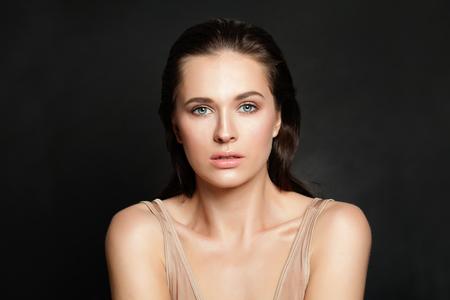 Schöne Frau mit natürlicher klarer Haut auf schwarzem Hintergrund