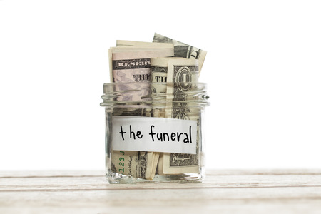 Saving jar with money for the funeral on white wooden table isolated Reklamní fotografie
