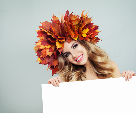Pretty autumn woman smiling and holding empty paper board background
