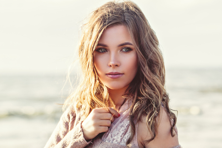 아름 다운 여자 얼굴 근접 촬영 초상화입니다. 바다 배경에 긴 곱슬 갈색 머리를 가진 예쁜 소녀. 완벽한 자연의 아름다움