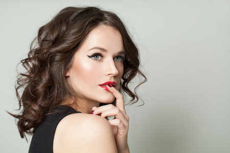 Hübsche vorbildliche Frau mit Make-up und brauner lockiger Frisur, Modeporträt