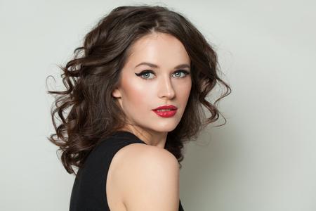 Hermosa mujer mirando a la cámara. Bonita modelo con maquillaje y retrato de cabello castaño rizado