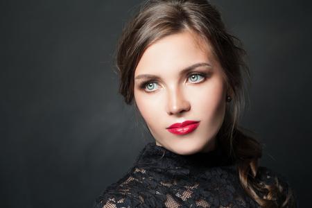 Femme élégante avec des cheveux de maquillage de lèvres rouges sur fond sombre Banque d'images