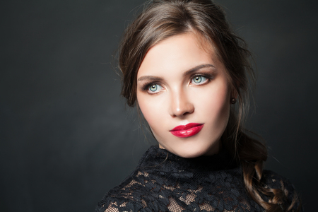 Mujer elegante con pelo de maquillaje de labios rojos sobre fondo oscuro Foto de archivo