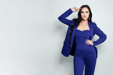 Fashion portrait of elegant model woman in jumpsuit standing against white background