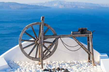 Santorini background card. Wooden wheel against sea