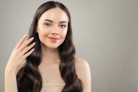 Ritratto di una bella donna bruna con pelle e capelli sani su sfondo grigio
