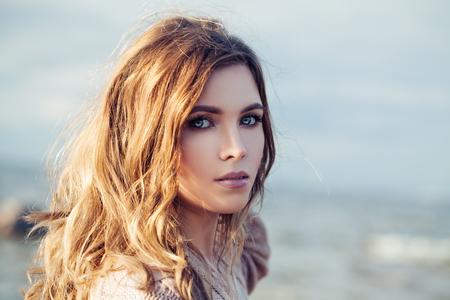Hermosa mujer sensual con pelo largo y rizado en día soleado