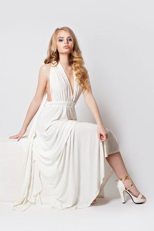 Hermosa mujer con piernas perfectas en zapatos de tacones. Bonita modelo en vestido blanco