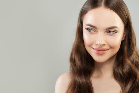 Portret van vrolijke vrouw met heldere huid en gezond krullend haar op grijze achtergrond. Mooi gezicht close-up. Huidverzorging en gezichtsbehandeling concept