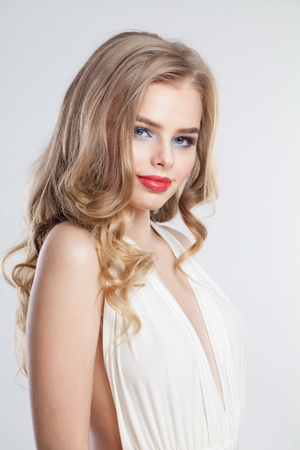 Beautiful young woman. Blonde model girl with makeup and long curly hairstyle