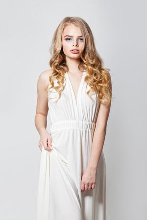 Blonde beauty. Pretty woman in white dress