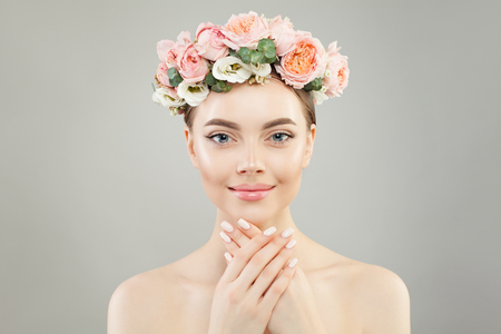 Young woman with healthy skin and roses flowers wreath