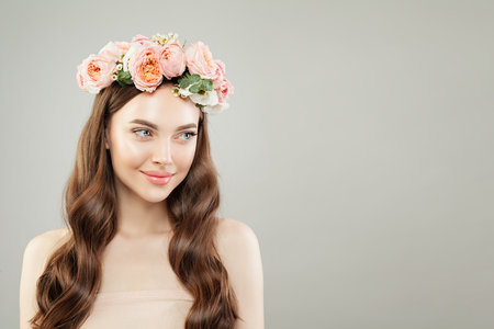 Portrait of beautiful smiling woman with clear skin, long shiny hair and flowers. Skincare and facial treatment concept