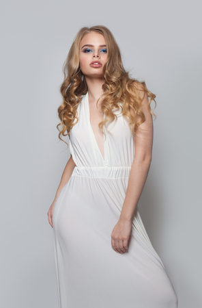 Attractive woman in white dress. Fashion model girl with blonde hair and makeup