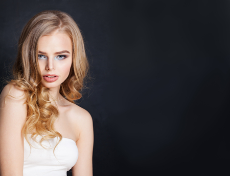 Beautiful blonde woman portrait. Pretty girl with blonde hair on black background Imagens