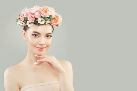 Cheerful young woman with clear skin and flowers on white background