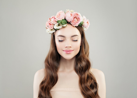 Natural beauty. Pretty woman enjoying. Model girl with clear skin, long brown curly hair and flowers Imagens
