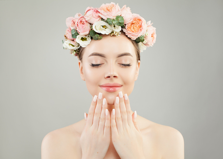 Portrait of perfect woman spa model with clear skin, manicured nails and flowers