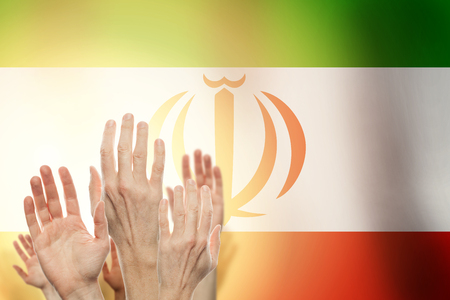 People raising hands and  flag Iran on background. Patriotic concept Imagens