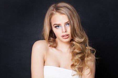 Ładna kobieta z długimi blond włosami na czarnym tle