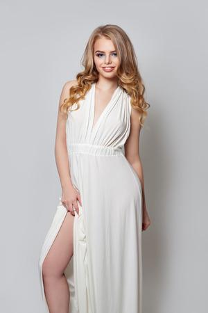 Elegant woman with blonde hair in trendy white dress portrait Imagens
