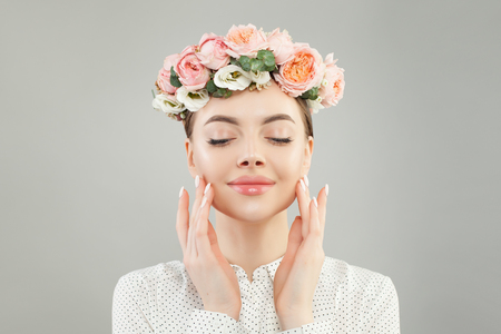Smiling woman with clear healthy skin and flowers. Skincare portrait