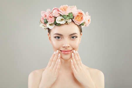 Beautiful woman face. Spa model girl with clear skin, hand with manicured nails and roses flowers on head