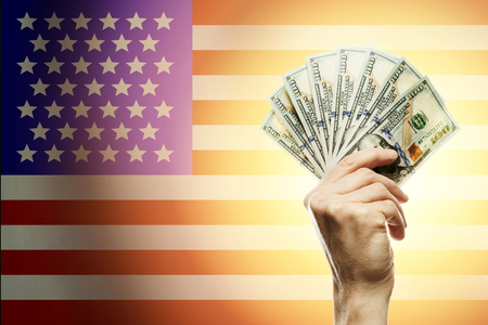 People raising hands dollars and American flag on background. Patriotic concept Imagens