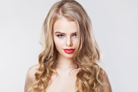 Beautiful young woman with curly hairstyle. Blonde woman with red lips makeup Imagens