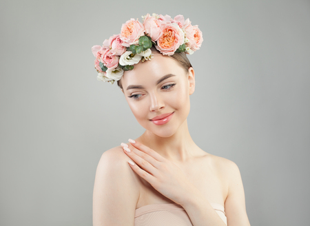 Beautiful model with clear skin and flowers on white background