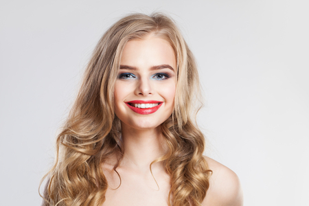 Smiling woman with blonde curly hairstyle. Pretty girl with red lips makeup