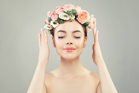 Young woman smiling. Pretty woman with clear skin and flowers