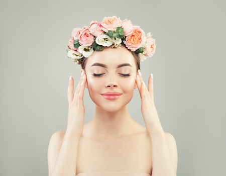 Beautiful woman with flowers and clear skin on gray background