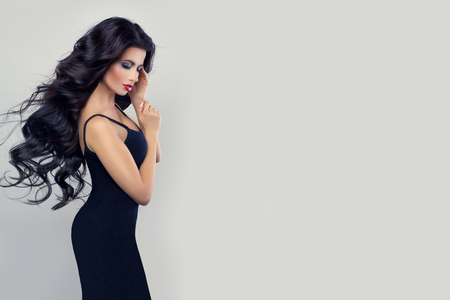 Beautiful brunette model woman with long perfect hair in black dress against white wall background Banco de Imagens