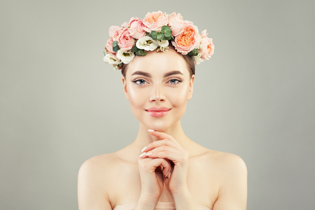 Beautiful healthy woman with clear skin and tender rose flowers. Skincare and facial treatment concept