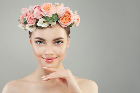 Pretty spa woman with clear skin and tender rose flowers portrait